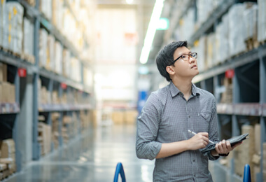an Asian male is checking goods in the warehouse